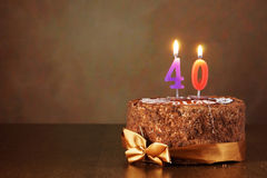De cake van de verjaardagschocolade met het branden van kaarsen als aantal veertig Stock Foto