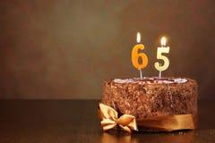 De cake van de verjaardagschocolade met het branden van kaarsen als nummer vijfenzestig Royalty-vrije Stock Foto