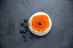De cake van het Pavlovaschuimgebakje met room, abrikozen en bosbessen op Th Royalty-vrije Stock Afbeelding