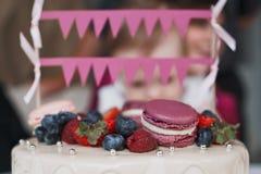 De cake van de kinderen` s verjaardag Op de cake zijn er frambozenbessen, bosbessen en aardbeien, purpere en roze makarons, decor stock afbeeldingen
