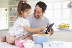 De Cakerecept van vaderand daughter following op Digitale tablet Stock Afbeeldingen
