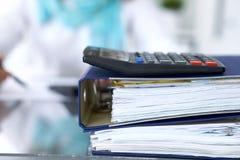 De calculator en de bindmiddelen met documenten wachten om door onderneemster of secretaresse terug in onduidelijk beeld worden v Stock Afbeelding