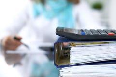 De calculator en de bindmiddelen met documenten wachten om door onderneemster of secretaresse terug in onduidelijk beeld worden v Stock Foto
