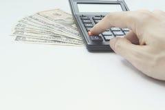 De calculator en de Dollargeldinvestering en bezit van het handgebruik voor Stock Afbeeldingen