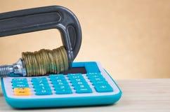 De calculator en de muntstukken drukten strak in een g-Klem stock fotografie