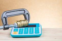 De calculator en de muntstukken drukten strak in een g-Klem royalty-vrije stock foto's
