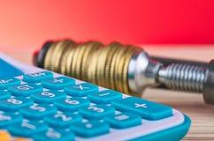 De calculator en de muntstukken drukten strak in een g-Klem stock afbeelding