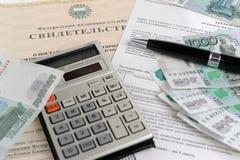 De calculator, het geld, de pen en de belasting handelen tegen de achtergrond van het certificaat Stock Afbeelding