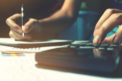De calculator met vrouwenhand berekent over uitgave op bureau bij ho Royalty-vrije Stock Foto