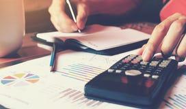 De calculator met vrouwenhand die financiën in huis doen en berekent a Royalty-vrije Stock Foto's