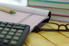 De calculator, de oogglazen, de pen, het ontvangstbewijs en de rekening boeken en gestapeld van boeken op de achtergrond Stock Fotografie