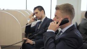 De call centreexploitanten spreken op telefoon terwijl het zitten in belangrijk bedrijf stock footage
