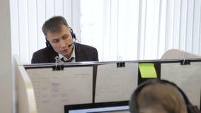 De call centrewerknemer spreekt terwijl het zitten bij werkplaats in bedrijf stock video