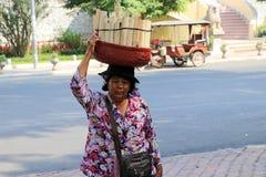De Cambodjaanse vrouwelijke straatventer zette de mand kleverige die rijst in kokosmelk wordt en in een sectie van bamboestam wor stock afbeelding