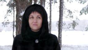 De camera beweegt dicht zich op rond de vrouw Een donkerbruin meisje in een zwarte laag bevindt zich in een bos of een park op de stock video