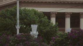 De camera beweegt zich van bomen aan een monumentaal gebouw stock videobeelden