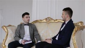 De camera daalt Twee knappe zakenlieden die in kostuums op een bank zitten die zaken bespreken stock video