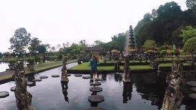 De camera gaat uit: de jonge vrouw loopt langs tegels in een vijver in een mooie Balinese tempel Tirta Gangga in Bali, langzame m stock videobeelden