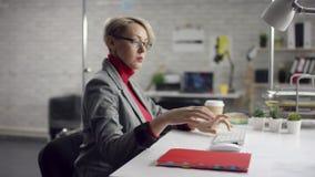 De camera glijdt rond freelancer` s handen typend op laptop toetsenbord in langzame motie Onderneemster die op kantoor werken met stock footage