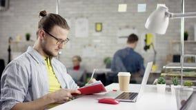 De camera glijdt rond freelancer` s handen typend op laptop toetsenbord in langzame motie Zakenman die op kantoor werken met stock videobeelden