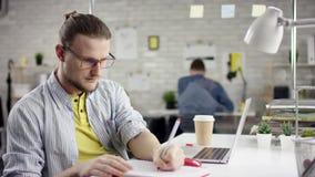 De camera glijdt rond freelancer` s handen typend op laptop toetsenbord in langzame motie Zakenman die op kantoor werken met stock video