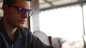 De camera glijdt van freelancer` s handen typend op laptop toetsenbord aan de knappe zakenman in glazen die werken aan stock videobeelden