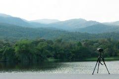 De camera met driepoot neemt beelden van mooie Reservoirs en bergen stock foto