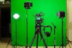 De camera op de driepoot, leidde schijnwerper, hoofdtelefoons en een richtingmicrofoon op een groene achtergrond De chromasleutel royalty-vrije stock afbeeldingen