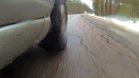 De camera opgezet op een auto wanneer zich het bewegen op de winterweg in bos het gaat ijzel De waterplonsen krijgen op camera stock footage