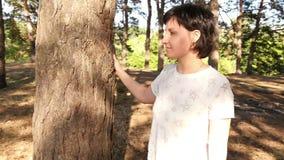 De camera roteert langzaam rond het meisje die zich door de boom in het bos bevinden stock videobeelden