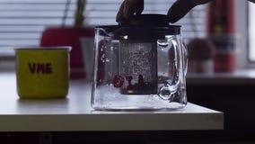 De camera toont lijst met grote die mok en glastheepot op lijst in keuken wordt geplaatst stock footage