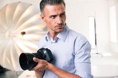 De camera van de fotograafholding en weg het kijken Royalty-vrije Stock Afbeelding