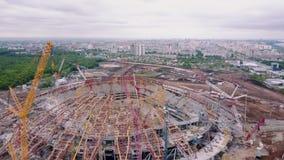 De camera vliegt over grote sportieve arena in aanbouw met stadspanorama op achtergrond stock video