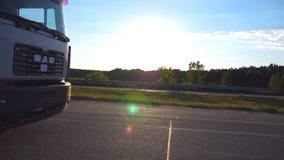 De camera volgt aan vrachtwagen het drijven op een weg in avond Vrachtwagenritten door het platteland met mooi landschap bij stock videobeelden