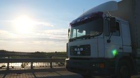 De camera volgt aan vrachtwagen het drijven op een weg Vrachtwagenritten door het platteland met mooi landschap bij achtergrond stock videobeelden