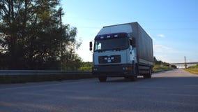 De camera volgt aan vrachtwagen het drijven op een weg Vrachtwagenritten door het platteland met mooi landschap bij achtergrond stock footage