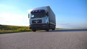 De camera volgt aan vrachtwagen het drijven op een weg Vrachtwagenritten door het platteland met mooi landschap bij achtergrond stock video