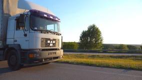 De camera volgt aan vrachtwagen het drijven op weg in avond Vrachtwagenritten door platteland met zonsondergang bij achtergrond b stock video