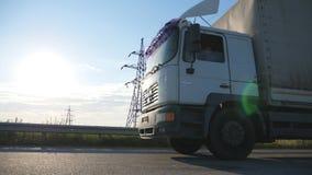 De camera volgt aan vrachtwagen op een weg Vrachtwagen het verzenden door het platteland met zonsondergang bij achtergrond Bodem  stock videobeelden