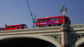 De camera volgt de rode bus van Londen kruisend de Brug van Westminster stock videobeelden