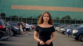 De camera volgt een jong aantrekkelijk brunette in het parkeerterrein stock videobeelden