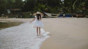 De camera volgt gelukkig jaar weinig 5-7 het oude meisje lopen langs exotisch tropisch oceaanstrand opwekte die grote strohoed dr stock video