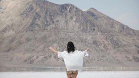 De camera volgt het jonge gelukkige vrije vrouw lopen naar berg met wapens open en vliegend haar bij zout woestijnmeer Utah stock videobeelden