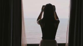 De camera volgt jonge mooie vrouw die aan de open donkere gordijnen van het ruimtevenster lopen genieten van verbazend oceaanmeni stock video