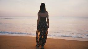 De camera volgt jonge toeristenvrouw in mooie kleding die naar zonsondergang op episch idyllisch exotisch toevlucht oceaanstrand  stock footage