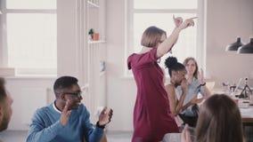 De camera volgt Kaukasische vrouwelijke leider die grappige dansgang van overwinning en succesviering in bureau langzame motie do stock videobeelden