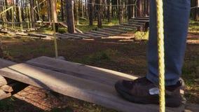 De camera volgt mensenbenen op kabelbrug in parkbomen stock videobeelden