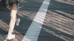De camera volgt vrouwelijke benen lopend langs asfalt en houten die weg met strepen, met mooie dunne schaduwen 4K worden behandel stock video