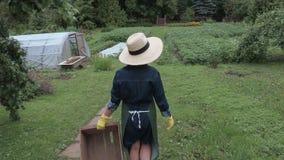 De camera volgt vrouwelijke tuinman met houten doos stock footage