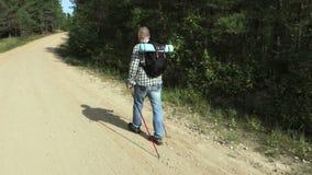 De camera volgt wandelaar die onderaan de weg lopen stock footage